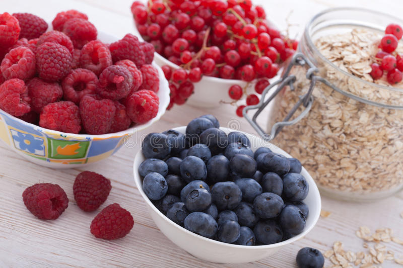 Breakfast - berries, fruit and muesli on white wooden stock images