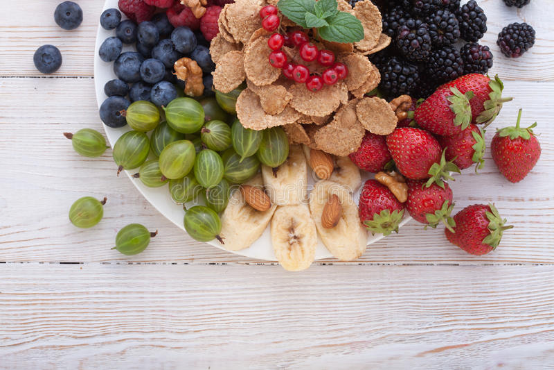 Breakfast - berries, fruit and muesli on white wooden stock photos