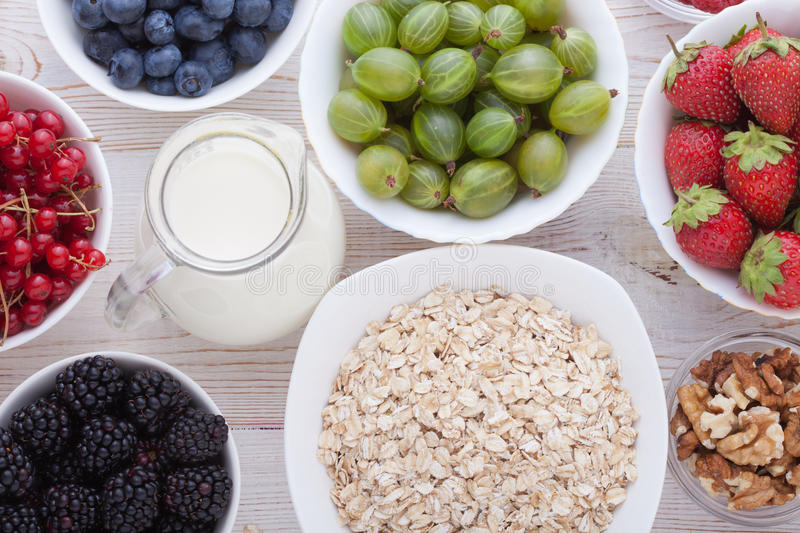 Breakfast - berries, fruit and muesli on white wooden stock photography