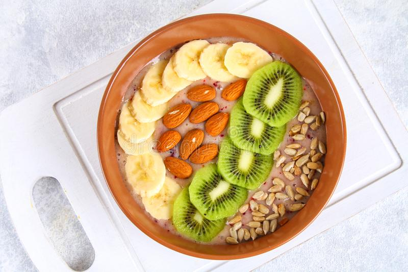 Breakfast berry smoothie bowl topped with bananas, berries, kiwi, almonds and sunflower seeds. Breakfast berry smoothie bowl topped with bananas, berries, kiwi stock photos