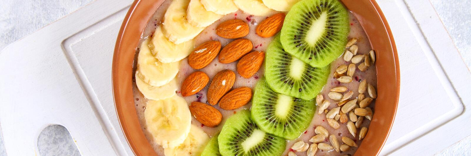 Breakfast berry smoothie bowl topped with bananas, berries, kiwi, almonds and sunflower seeds. Breakfast berry smoothie bowl topped with bananas, berries, kiwi stock photography