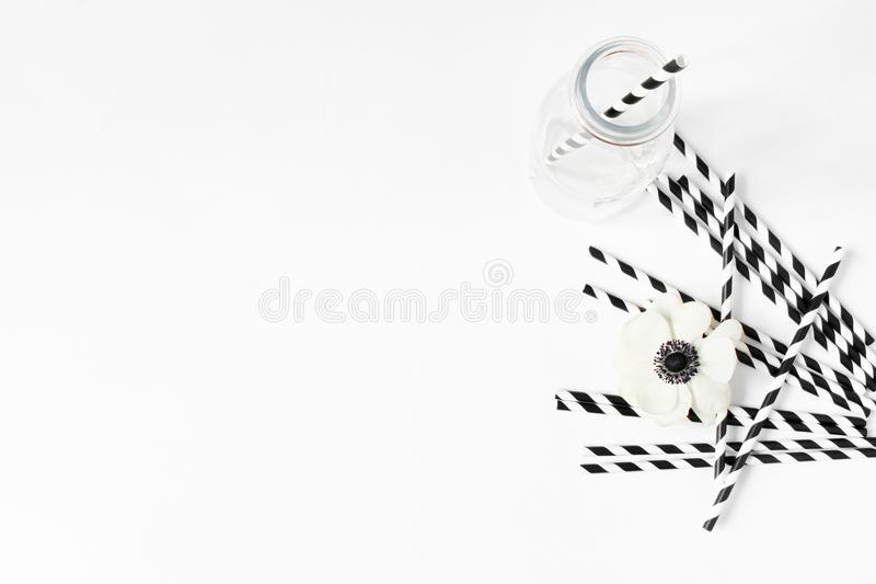 Breakfast or birthday party desktop scene. Composition with empty milk glass jar, black and white drinking paper straws stock photos