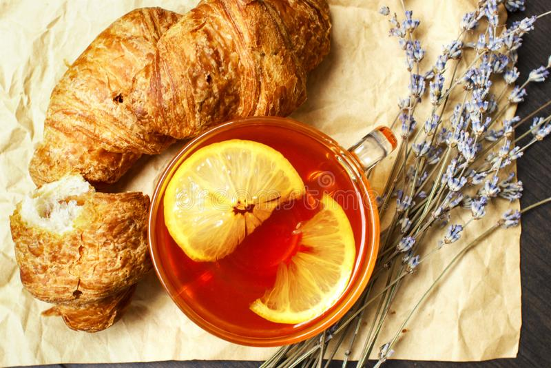 Breakfast with black hot tea and fresh croissants on a paper background with bouquet of lavender stock photos