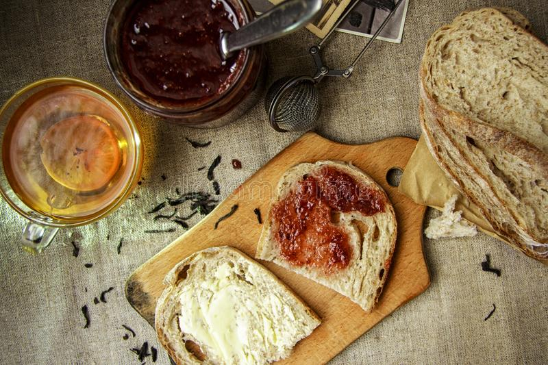 Flat lay. Breakfast with black tea, strawberry jam and sliced fresh bread with butter on a linen napkin stock photos