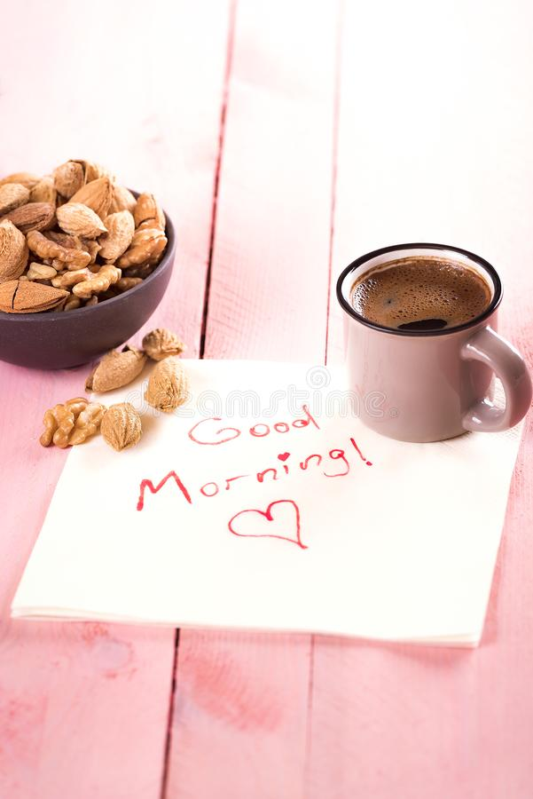 Bowl of nuts and a good morning text. Breakfast with a bowl of almonds in shell, walnuts and a cup of aromatic coffee on a napkin with the words good morning royalty free stock image