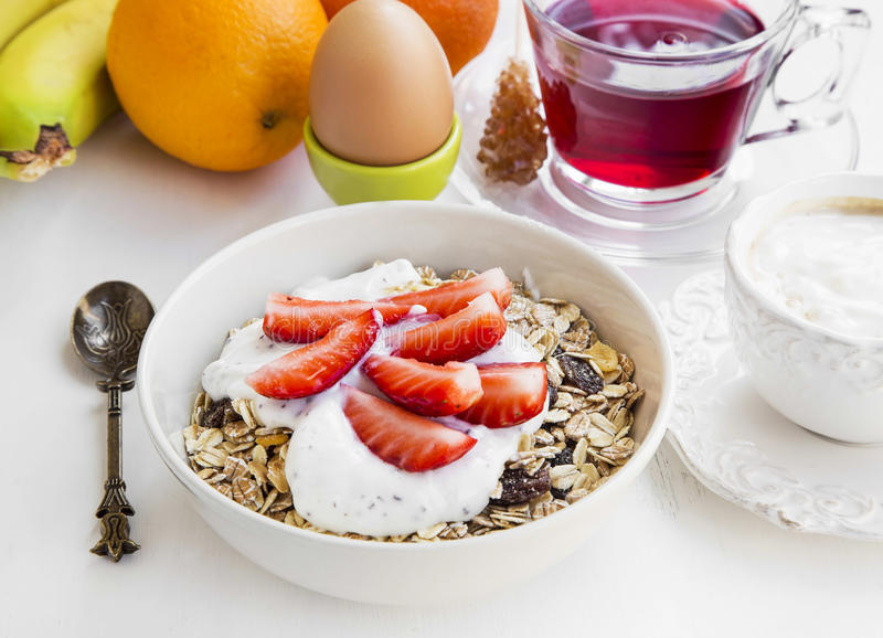 Breakfast bowl with muesli,yogurt and strawberries, tea and fruits in background stock photos