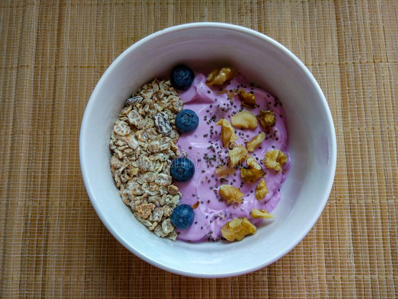 Breakfast bowl with nuts, blueberry, granola and chia seed from above royalty free stock image