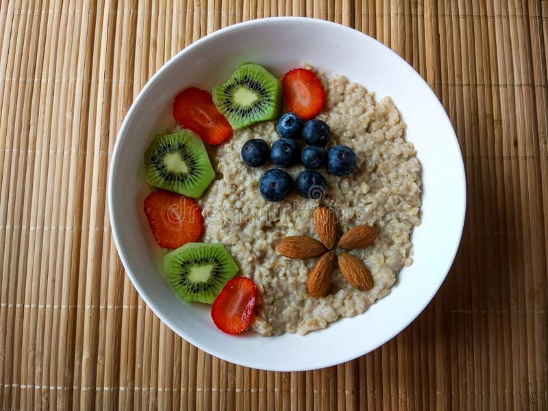 Breakfast bowl with strawberries, kiwi and blueberries, with cereals and almonds forming a flower royalty free stock photography