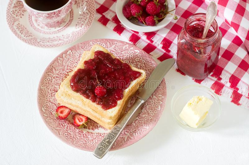 Breakfast of bread toasts with butter and strawberry-rhubarb jam, served with tea. Rustic style. royalty free stock photography