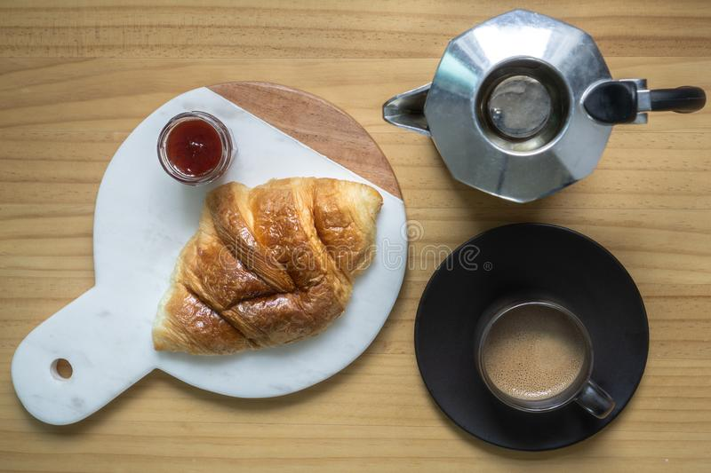 Black coffee with creama made by Moka pot home brew in black espresso cup served with delicious buttery croissant and strawberry j stock images
