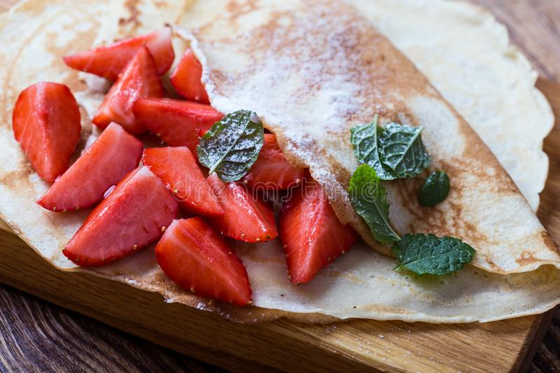 Breakfast or brunch, crepes with fresh summer strawberries and powdered sugar stock photo