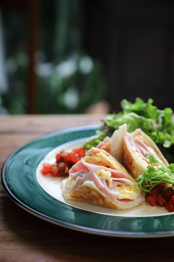 Breakfast burrito ham and eggs with salad vintage style stock photography