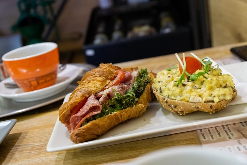 Sandwich and Kaiser with ham, salad, cheese and smashed eggs, coffee in the background. royalty free stock photos