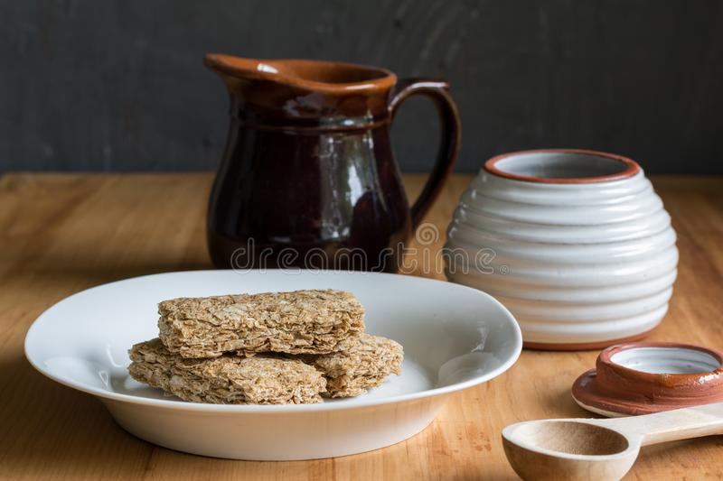 Breakfast cereal bars in bowl, with milk and honey jar in background. Cereal bars in bowl, with milk jug and honey jar in background - Preparation to eat stock image