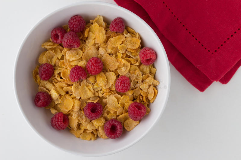 Breakfast cereal of cornflakes and raspberries on white background stock photo
