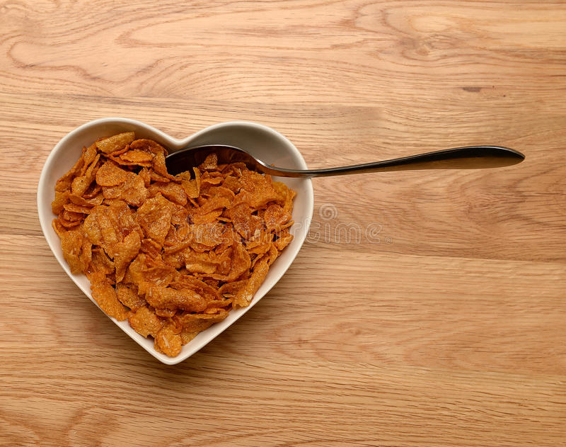 Breakfast cereal in heart shaped bowl. With spoon on wooden table stock photo