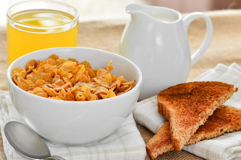 Breakfast cereal with toast and juice. Breakfast cereal with toast and juice, with a jug of fresh milk to pour on the cereals stock photography