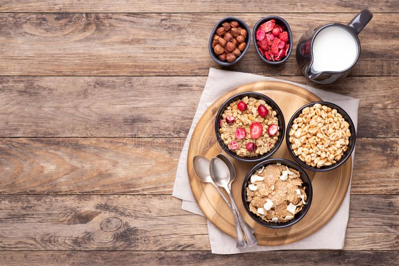 Breakfast cereals in bowls with a jug of milk on rustic wooden table, top view with copy space stock image