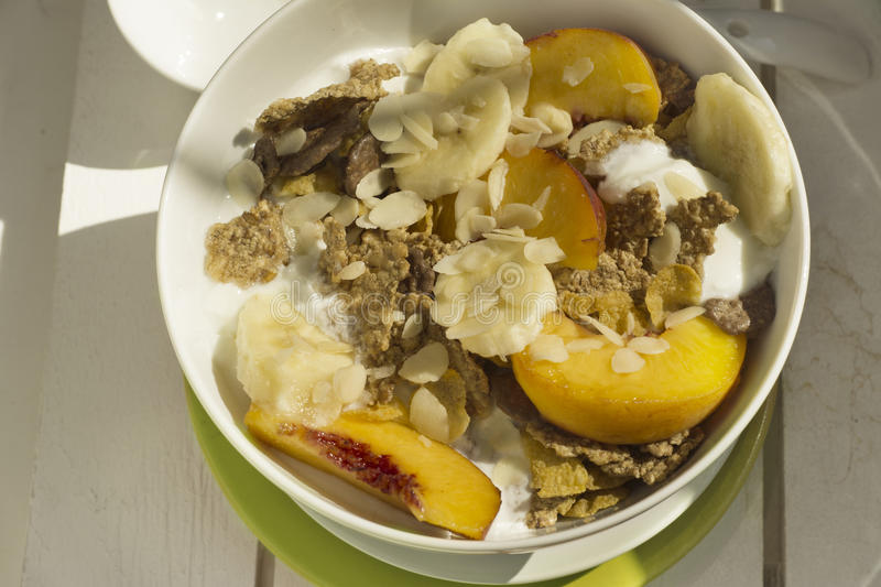Breakfast cereals and fruit on white wood stock images