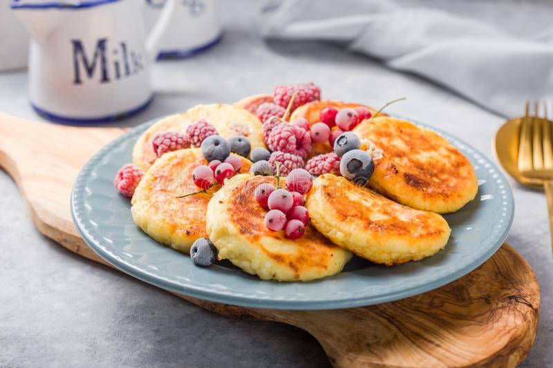 Breakfast with cheesecake,  fresh berries .  Cottage cheese pancakes or curd fritters. Russian syrniki or sirniki royalty free stock images