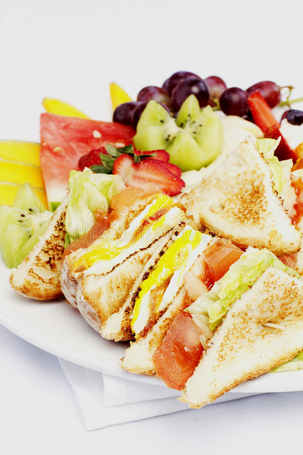 Breakfast club sandwich and assorted fruits. On white plate royalty free stock photos