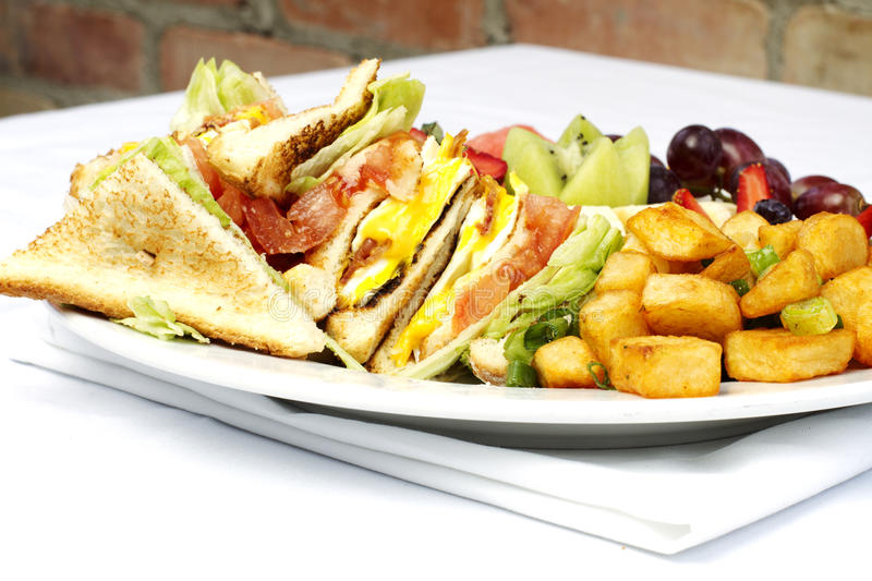 Breakfast club sandwich and assorted fruits. On white plate stock photo
