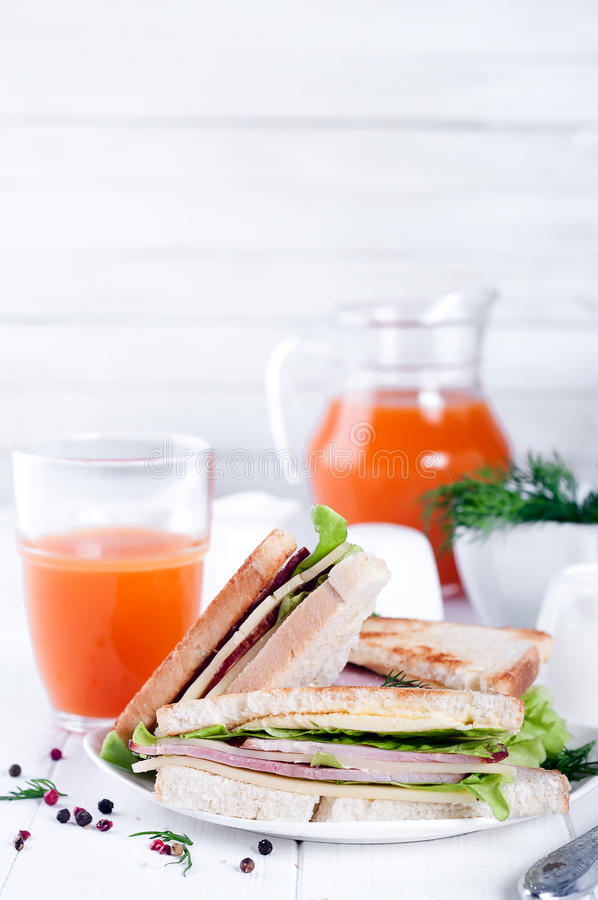 Breakfast with club sandwich and juice. Club sandwich with orange juice on a background wooden royalty free stock photo