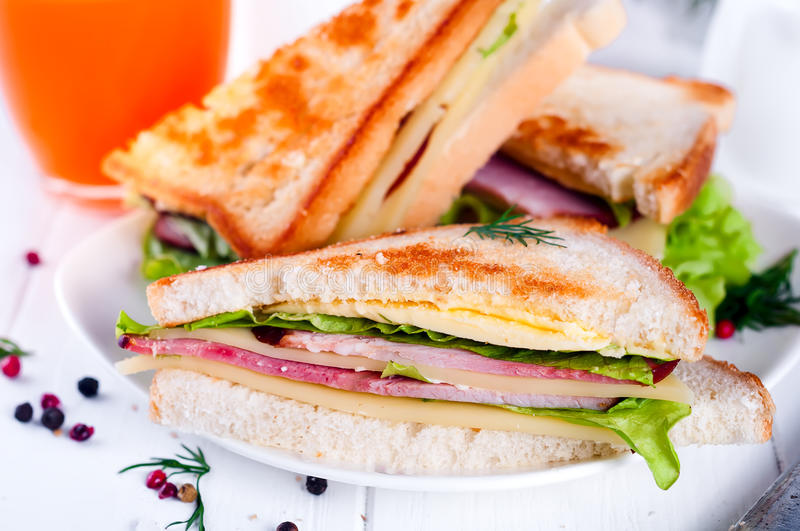 Breakfast with club sandwich and juice. Club sandwich with orange juice on a background wooden royalty free stock photos