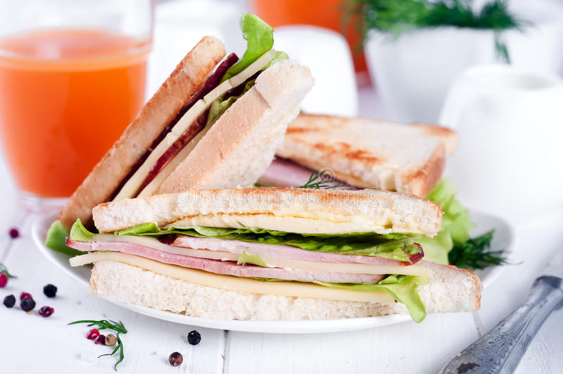 Breakfast with club sandwich and juice. Club sandwich with orange juice on a background wooden stock photos