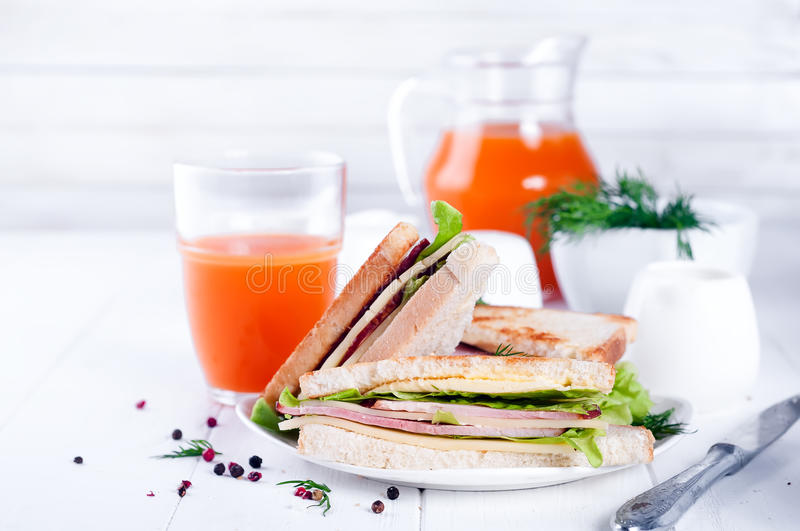 Breakfast with club sandwich and juice. Club sandwich with orange juice on a background wooden stock image