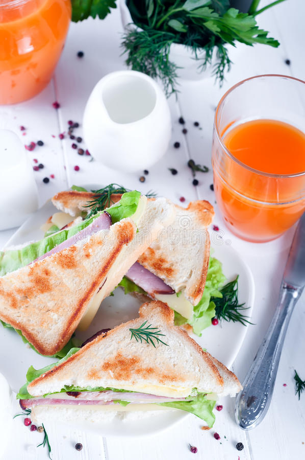 Breakfast with club sandwich and juice. Club sandwich with orange juice on a background wooden. View from above stock photography