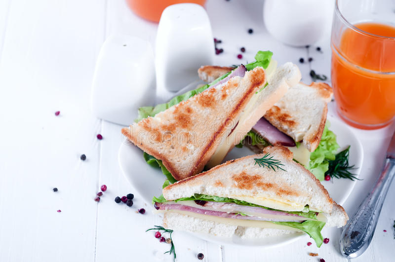 Breakfast with club sandwich and juice. Club sandwich with orange juice on a background wooden. View from above royalty free stock image