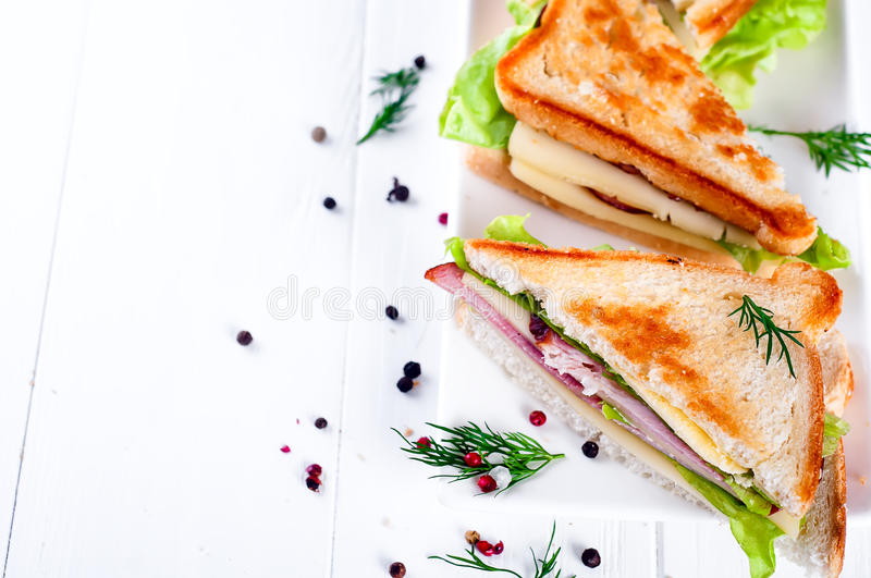 Breakfast with club sandwich and juice. Club sandwich with sausage on a white plate on a white background wooden. View from above stock image
