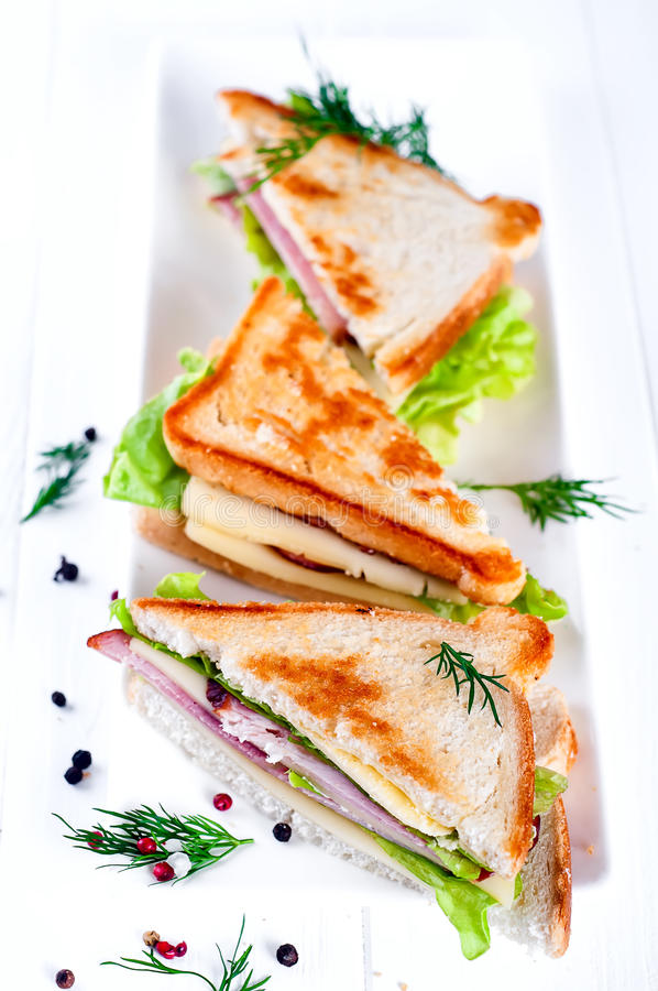 Breakfast with club sandwich and juice. Club sandwich with sausage on a white plate on a white background wooden. View from above stock photography