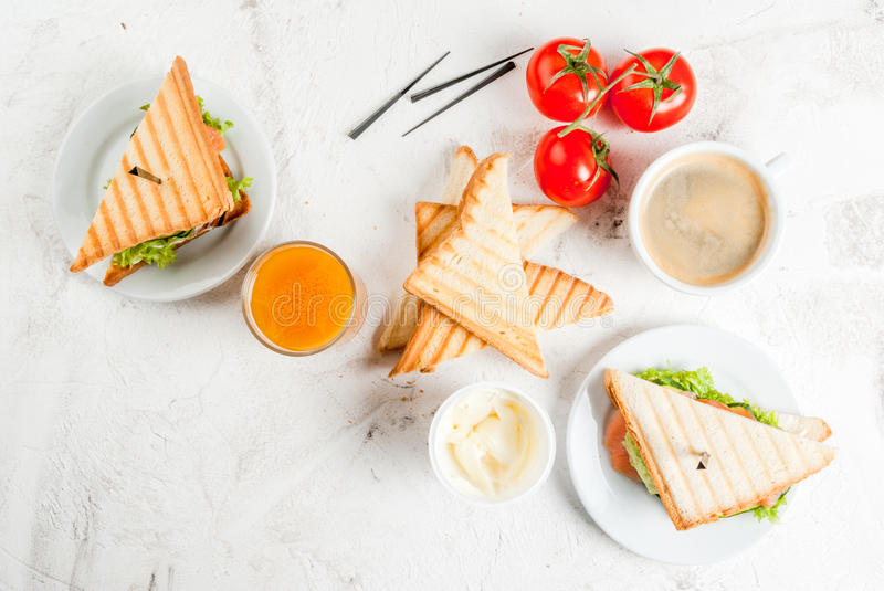 Breakfast with club sandwiches. With fresh tomatoes, lettuce and cucumbers salmon trout, coffee and freshly squeezed juice, on white stone concrete table top royalty free stock images