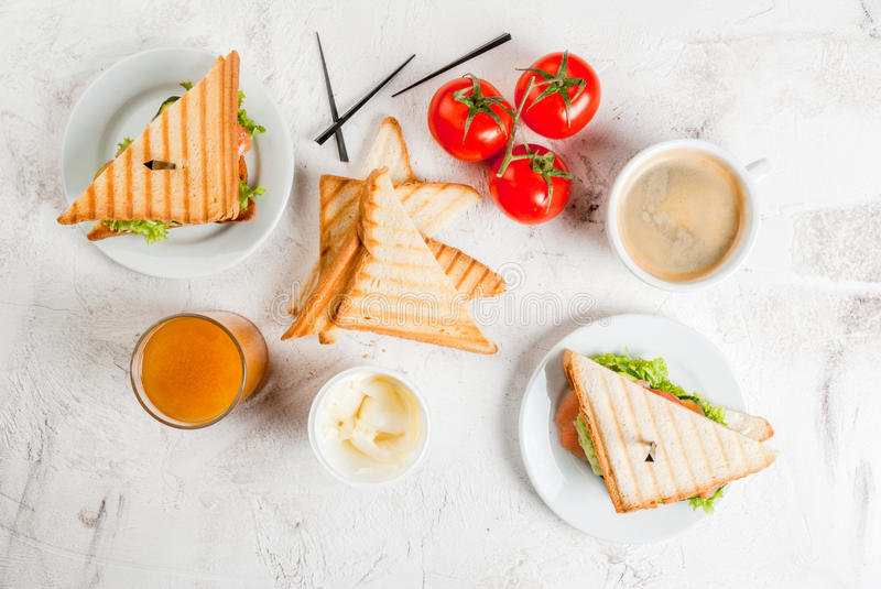 Breakfast with club sandwiches. With fresh tomatoes, lettuce and cucumbers salmon trout, coffee and freshly squeezed juice, on white stone concrete table top stock photos