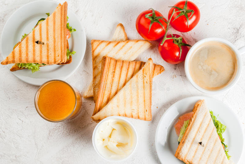 Breakfast with club sandwiches. With fresh tomatoes, lettuce and cucumbers, salmon trout, coffee and freshly squeezed juice, on white stone concrete table top royalty free stock images