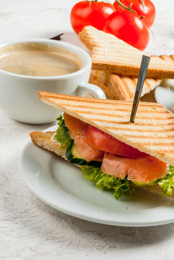 Breakfast with club sandwiches. With fresh tomatoes, lettuce and cucumbers salmon trout, coffee and freshly squeezed juice, on white stone concrete table close stock images