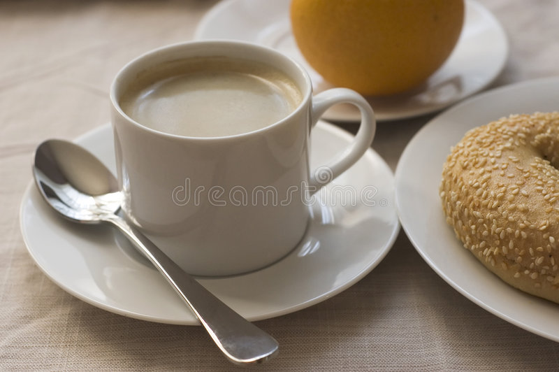 Breakfast and coffee. Coffee, bagel, orange breakfast royalty free stock photos