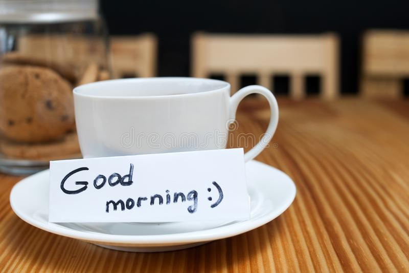 Breakfast coffee biscuit white cup good morning. Breakfast ritual of coffee and biscuits. white cup with a wishing of good morning on the wooden table royalty free stock photo
