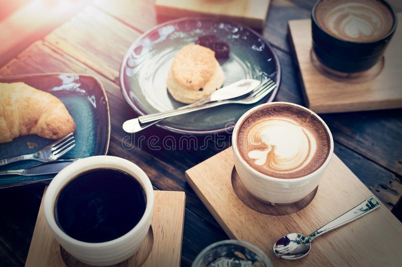 Breakfast with coffee and bread on wooden table. Under sunlight, Vintage color tone royalty free stock photos