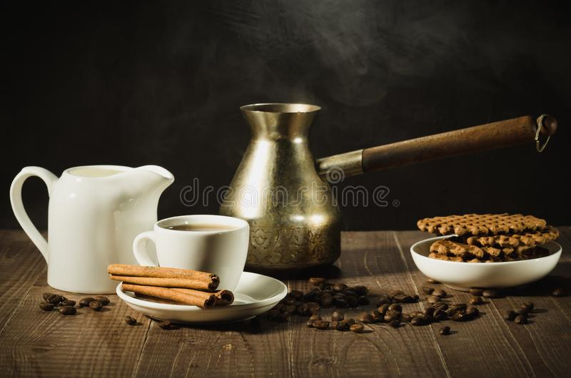 breakfast with coffee and cookies/coffee cup with cinnamon, old pot, creamer and chocolate cookies on a wooden table. selective royalty free stock photography