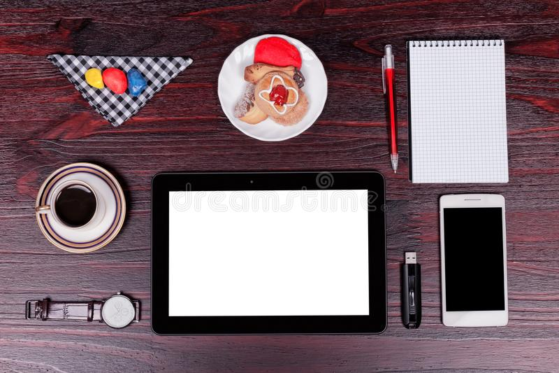 Breakfast with coffee and cookies next to the tools of your online work on mahogany wood. Background stock photos