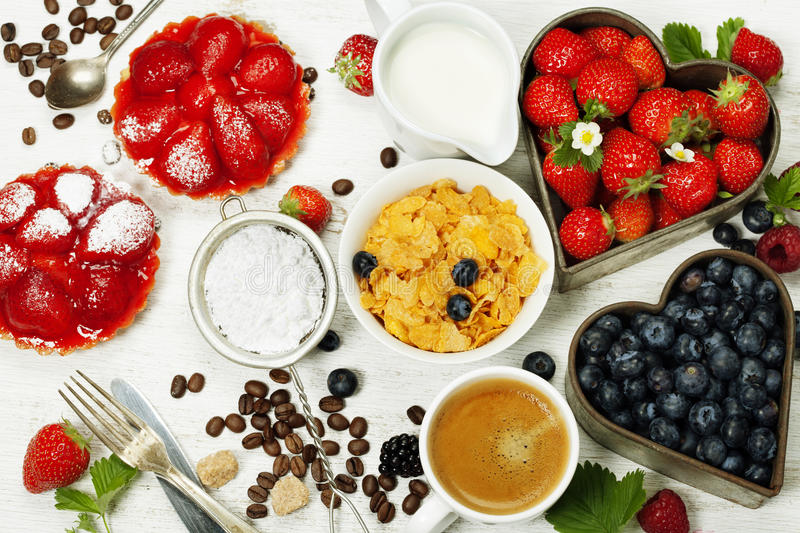 Breakfast with coffee, corn flakes, milk, tartlets and berry. On wooden background stock photography