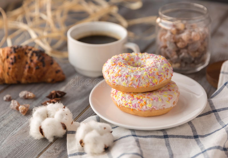 Breakfast of coffee. Cup of coffe with sweet donuts and chocolate croissant and bank sugar and cotton flowers and hay on a wooden background stock image
