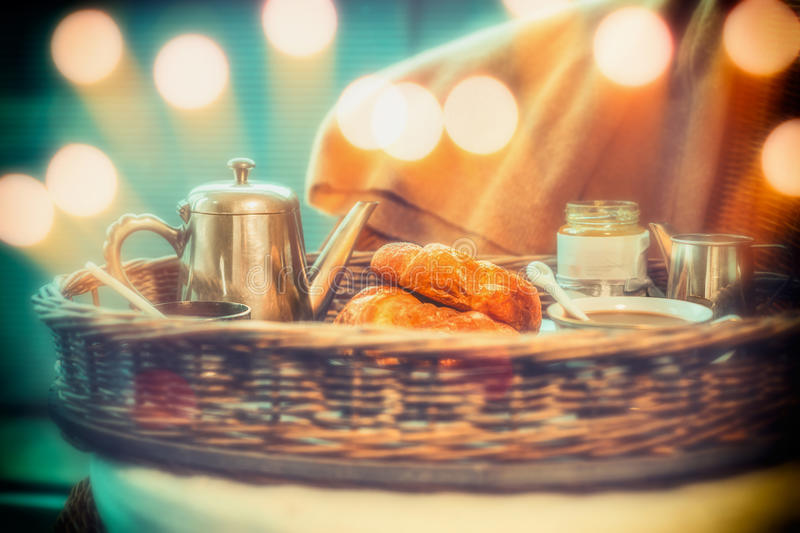 Breakfast with coffee pot and croissants on tray with bokeh. Lighting royalty free stock photos