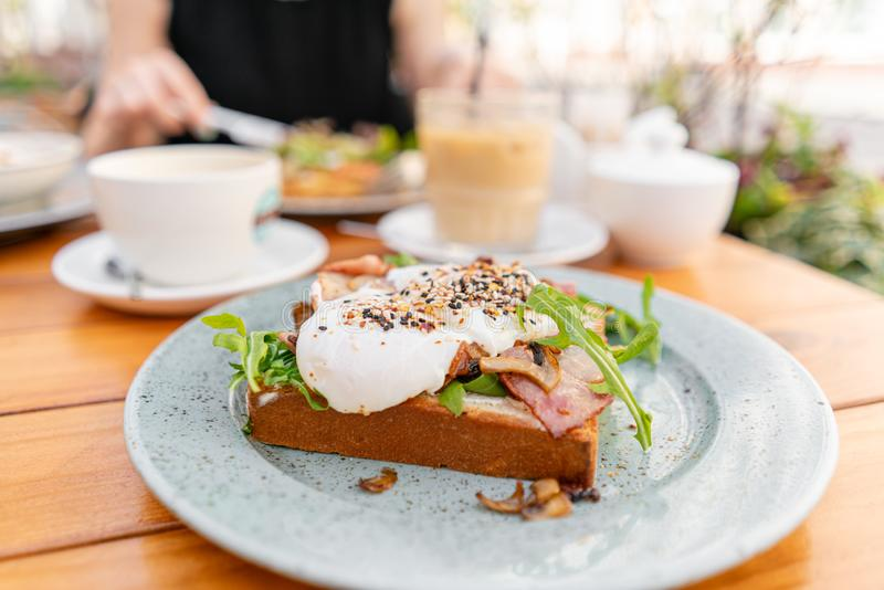 Breakfast and coffee in the summer cafe. Sandwich on a bun brioche with bacon, mushrooms, arugula and poached egg stock photos