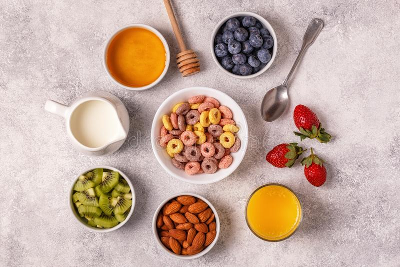 Breakfast with colorful cereal rings, fruit, milk, juice. stock photo