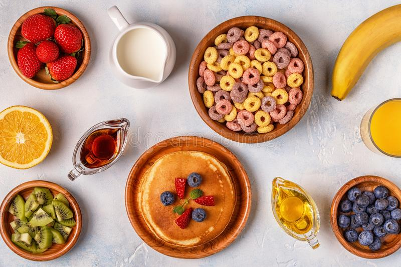 Breakfast with colorful cereal rings, pancakes, fruit, milk, juice. royalty free stock photos