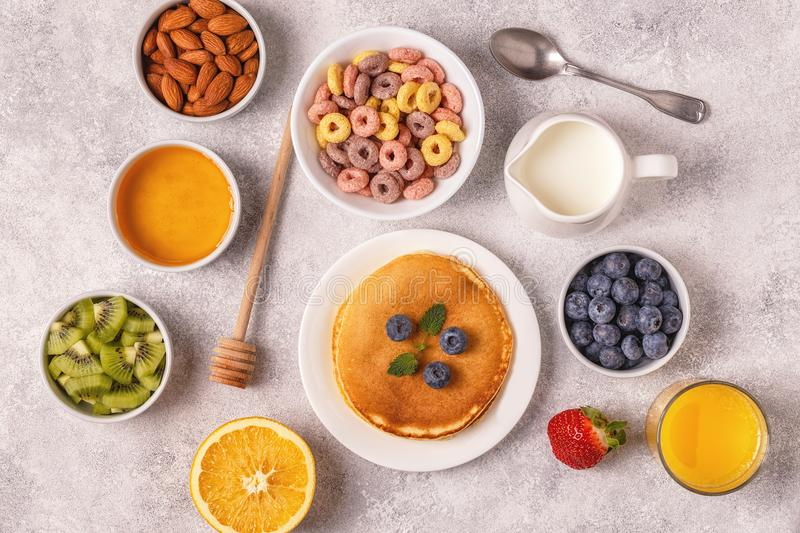 Breakfast with colorful cereal rings, pancakes, fruit, milk, juice. royalty free stock photography